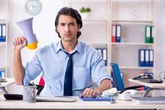 The young male businessman employee unhappy with excessive work. Young male businessman employee unhappy with excessive work stock images