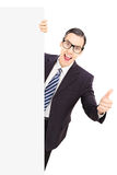Young male businessman giving thumb up, standing behind blank pa Royalty Free Stock Image