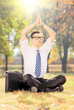 Young male businessman practicing yoga in park Stock Images