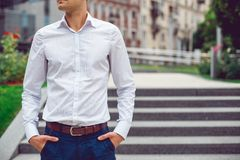 Young male businessman in shirt and blue pants. Hands in pockets. Hotizontal mockup Stock Images