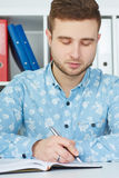 Young male businessman takes notes sitting at office. Royalty Free Stock Images