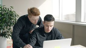 Young male businessmen discussing business at table with laptop in modern office. Young male businessmen discussing business at table with laptop in modern stock video