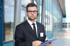 Young male call center operator in suit. Agains building Royalty Free Stock Photo
