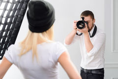 Young male cameraman during genuine work. Shooting process. Young male professional cameraman uses his camera during photographing royalty free stock photography