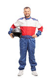 Young male car racer in overalls holding a helmet Royalty Free Stock Image