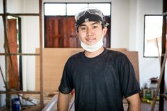 Young male carpenter portrait in workshop. Interior Royalty Free Stock Photography