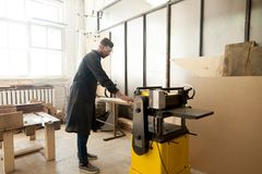 Jointer in protective workwear processing wood on stationary pow Royalty Free Stock Photos