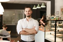 Young caucasian businessman standing with at cafe. Young male caucasian businessman standing with at cafe. Concept of business and success royalty free stock image