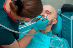 Young male checkups his teeth at the dentist doctor Stock Photo
