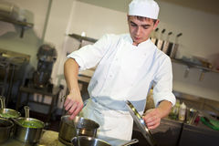 Young male chef cooking meal. At the stove stirring food in a pan royalty free stock photos
