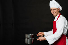Young male chef holding empty vessels Stock Photo