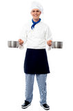 Young male chef holding empty vessels Royalty Free Stock Image