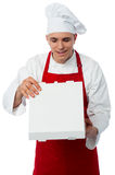 Young male chef holding pizza box Stock Photo
