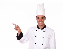 Young male chef pointing to his right Stock Images