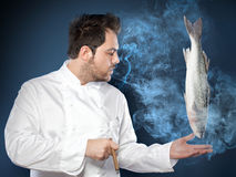 Young male chef with seabass fish Royalty Free Stock Photo
