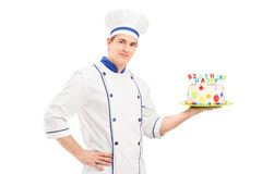 Young male chef in a uniform holding a decorated birthday cake. Isolated on white background Stock Photo
