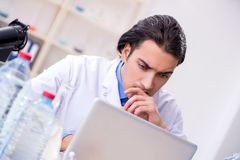 Young male chemist experimenting in lab. The young male chemist experimenting in lab royalty free stock images