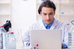 Young male chemist experimenting in lab. The young male chemist experimenting in lab stock photography