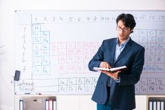The young male chemistry teacher in front of periodic table. Young male chemistry teacher in front of periodic table royalty free stock photography