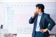 The young male chemistry teacher in front of periodic table. Young male chemistry teacher in front of periodic table stock photography