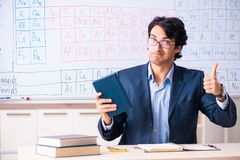 The young male chemistry teacher in front of periodic table. Young male chemistry teacher in front of periodic table royalty free stock photos