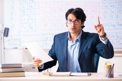 The young male chemistry teacher in front of periodic table. Young male chemistry teacher in front of periodic table stock image