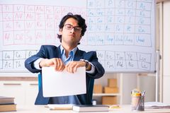 The young male chemistry teacher in front of periodic table. Young male chemistry teacher in front of periodic table stock photo