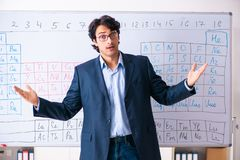 The young male chemistry teacher in front of periodic table. Young male chemistry teacher in front of periodic table stock photos