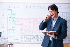 The young male chemistry teacher in front of periodic table. Young male chemistry teacher in front of periodic table royalty free stock image