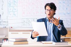 The young male chemistry teacher in front of periodic table. Young male chemistry teacher in front of periodic table royalty free stock photo