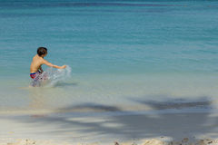 Young Male Child Splashing Water in the Ocean with Shadow of Palm Tree on Sandy Beach Stock Photos