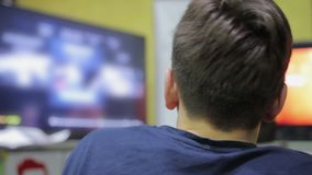 Young male choosing video game, looking at TV screen, leisure time and hobby. Stock footage stock footage