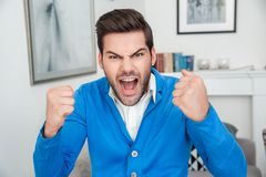 Young man patient waiting psychology session shouting emotional. Young male client waiting psychology therapy shouting at camera angry emotional Stock Photos