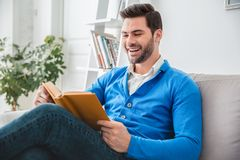Young man patient waiting psychology session laughing on book. Young male client waiting psychology therapy sitting on sofa reading book laughing funny story Stock Photography
