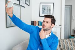 Young man patient waiting psychology session taking selfie photos. Young male client waiting psychology therapy taking selfie photos on smartphone posing Royalty Free Stock Photos