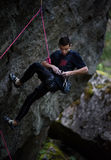 Young male climber climbing with rope and carbines, looking for next grip on a big rocky wall. Summer time. Climbing equipment. Rock climber on a challenging royalty free stock images