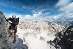 Young male climber on an exposed Via Ferrata in the Dolomites. Young male climber on a steep and exposed Via Ferrata in the South Tyrol in the Italian Dolomites Stock Photos