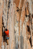 Young male climber hanging by a cliff. Royalty Free Stock Images