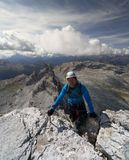 Young male climber reaches the summit after doing a Via Ferrata in the Italian Dolomites. With a great view behind Stock Images