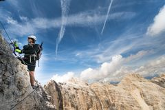 Young male climber on an exposed Via Ferrata in the Dolomites. Young male climber on a steep and exposed Via Ferrata in the South Tyrol in the Italian Dolomites Stock Photography