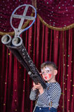 Young Male Clown Aiming Large Rifle on Stage Royalty Free Stock Image