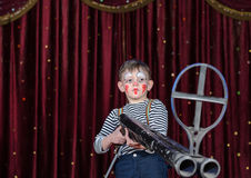 Young Male Clown Aiming Large Rifle on Stage Royalty Free Stock Photos