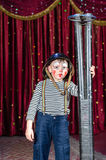 Young Male Clown Holding Large Rifle on Stage. Young Boy Wearing Clown Make Up and Military Helmet Standing on Stage with Large Prop Shot Gun Rifle in front of Royalty Free Stock Image