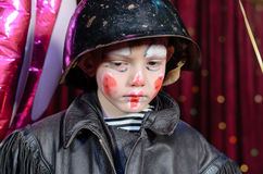 Young Male Clown Staring Solemnly Downward. Head and Shoulders Close Up of Young Boy Wearing Clown Make Up, Leather Jacket and Helmet Staring Solemnly Downward Royalty Free Stock Photo