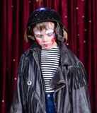 Young Male Clown Staring Solemnly Downward. Head and Shoulders Close Up of Young Boy Wearing Clown Make Up, Leather Jacket and Helmet Staring Solemnly Downward Stock Image