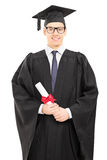 Young male college graduate posing with diploma in hand Stock Image
