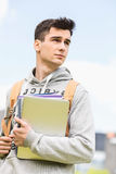 Young male college student holding books while looking away outdoors Royalty Free Stock Photos