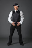 Young male confident male posing in gangster style suite. Studio isolated on gray background Royalty Free Stock Photo