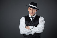 Young male confident male posing in gangster style suite. Studio isolated on gray background Stock Photos