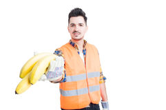 Young male constructor with gloves offering some bananas. As healthy break concept isolated on white royalty free stock photo